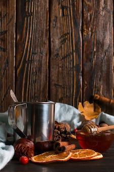 Caneca de ferro com café preto, mel, especiarias, sobre um fundo de um cachecol, folhas secas em uma mesa de madeira. clima de outono, uma bebida quente. copyspace.