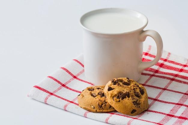 Caneca de leite com biscoitos no guardanapo sobre o fundo branco