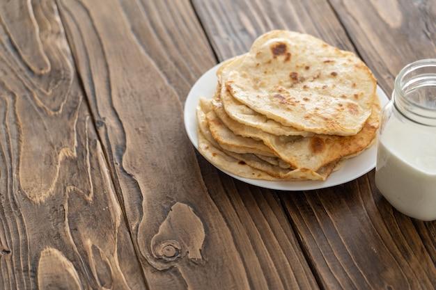 Caneca de leite e um prato de tortilhas de milho frito em uma mesa de madeira texturizada a vista de cima
