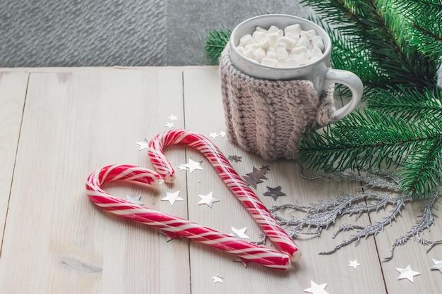 Caneca de marshmallows e bastões de doces cercados por enfeites de natal em uma mesa de madeira