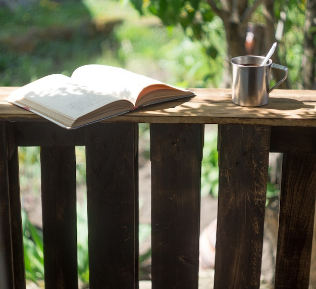 Caneca de metal e livro no terraço de madeira