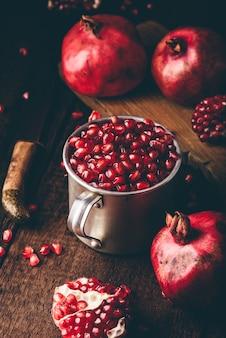 Caneca de metal rústica cheia de sementes de romã. frutas inteiras e pedaços de romã na mesa de madeira escura.