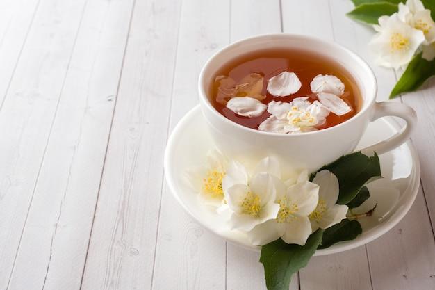 Caneca de tisana com as pétalas de flores do jasmim em um fundo claro.