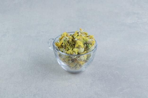 Caneca de vidro cheia de flores amarelas na mesa de pedra.