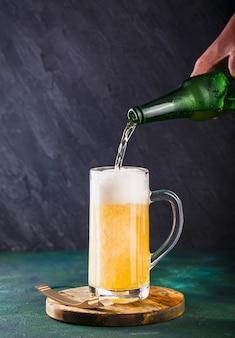 Caneca de vidro com cerveja com espuma e gotas de água em verde escuro