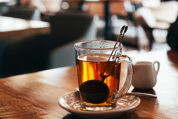 Caneca de vidro de chá quente em um café com fundo borrado. luz natural