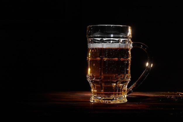 Caneca de vidro grande de cerveja no espaço de parede de madeira escura para texto horizontal