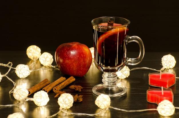 Caneca de vinho quente com especiarias, velas em forma de coração, paus de canela, anis estrelado. iluminação de lanternas de vime sobre uma mesa de madeira preta