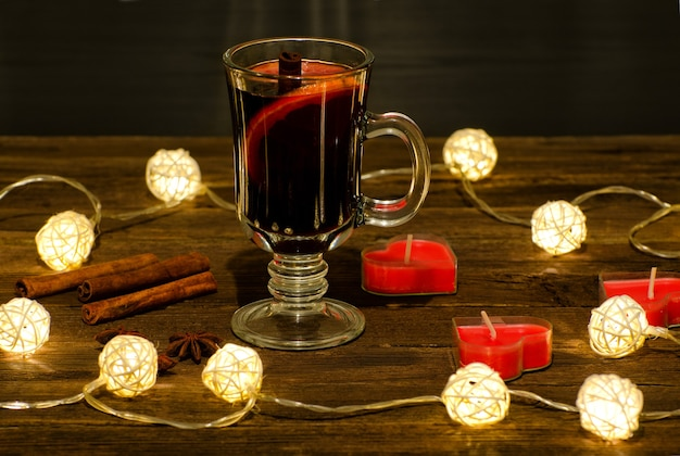 Caneca de vinho quente com especiarias, velas em forma de coração sobre uma mesa de madeira, uma guirlanda de lanternas. paus de canela, anis
