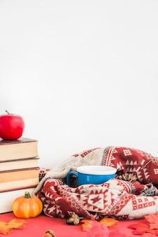 Caneca e cobertor perto de frutas falsas e livros