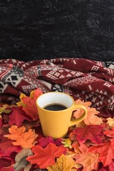 Caneca em folhas perto de cobertor