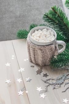 Caneca fofa cheia de marshmallows cercada por enfeites de natal na mesa