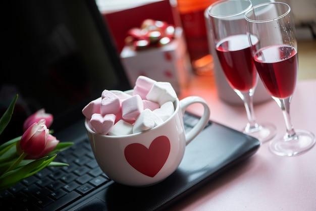 Caneca grande de chocolate quente com marshmallows e duas taças de vinho tinto no teclado preto do laptop