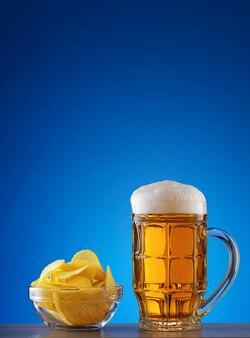 Caneca lapidada de cerveja light com espuma e batatas fritas no prato