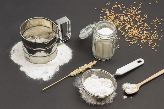 Caneca para peneirar farinha e peneira pequena com farinha espigão de trigo e colher de pau grãos de trigo na mesa superfície preta vista superior