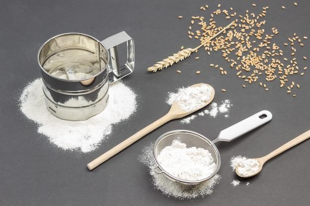 Caneca para peneirar farinha e peneira pequena com farinha, espigueta de trigo, colher de pau e grãos de trigo na mesa