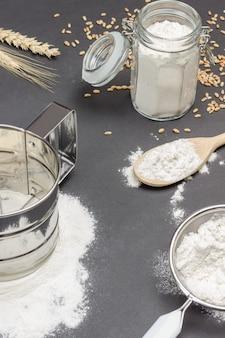 Caneca para peneirar farinha e peneira pequena com farinha, jarra de vidro com farinha, espigueta de trigo e colher de pau com grãos de trigo na mesa
