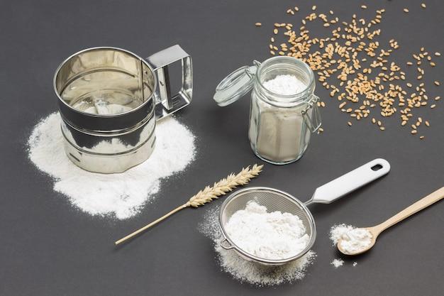 Caneca para peneirar farinha e peneira pequena com farinha, jarra de vidro com farinha, espigueta de trigo e colher de pau