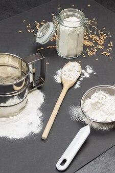 Caneca para peneirar farinha e peneira pequena com farinha jarra de vidro e colher de pau com farinha grãos de trigo na mesa superfície preta vista superior