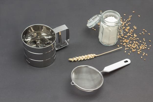 Caneca para peneirar farinha e peneira pequena, jarra de vidro com farinha e espiguetas de trigo