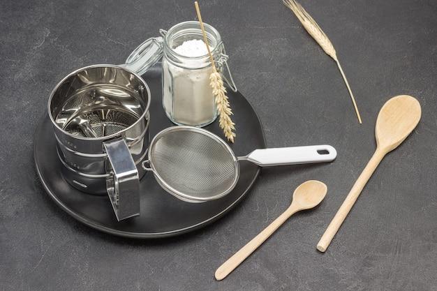 Caneca para peneirar farinha e peneira pequena, jarra de vidro com farinha na placa preta, espigas de trigo e colheres de madeira
