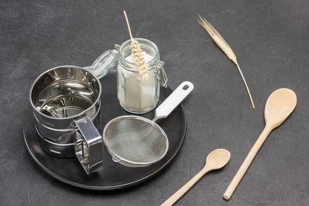 Caneca para peneirar farinha e peneirar pequeno frasco de vidro com farinha em placa preta espigão de trigo e colher de madeira superfície preta vista superior