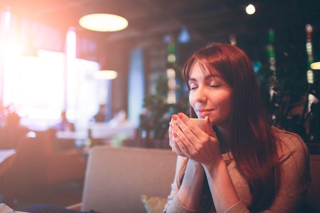 Caneca quente de chá com mãos de mulher. linda mulher tomando café no restaurante