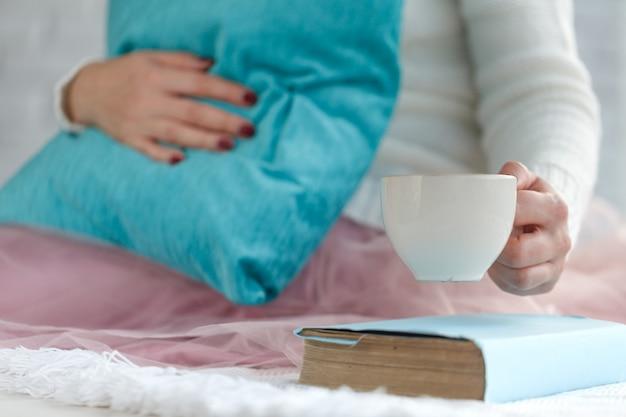 Caneca quente de chá com mãos de mulher na camisola de lã retrô