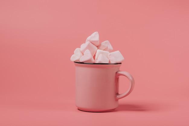 Caneca rosa cheia de marshmallows em forma de coração