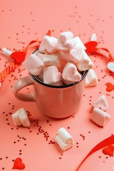 Caneca rosa em uma superfície rosa cheia de marshmallows em forma de coração.