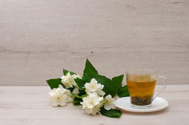 Caneca transparente com chá verde, um ramo de jasmim no fundo de madeira