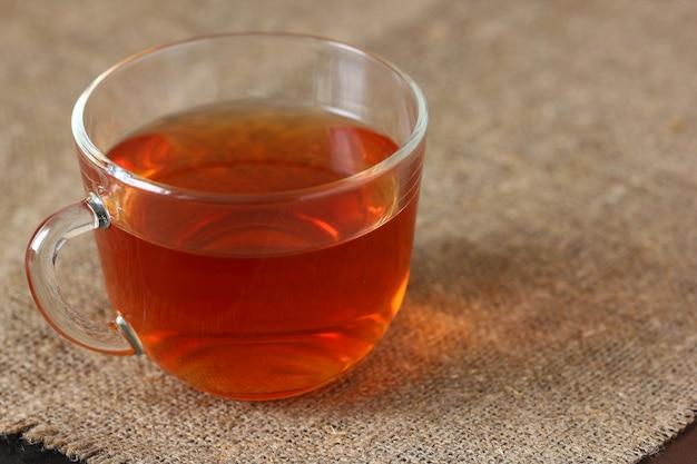Caneca transparente de vidro com chá preto na toalha de mesa de estopa áspera.