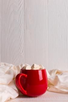 Caneca vermelha com cacau e marshmallows em um fundo de cachecol de mesa branca. clima de outono, uma bebida quente. copyspace.