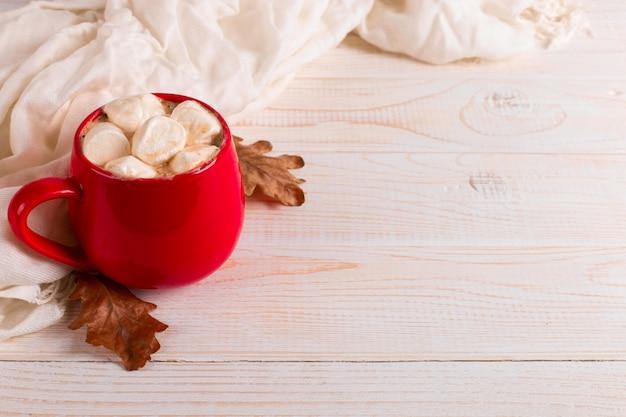 Caneca vermelha com cacau e marshmallows, sobre um fundo de um cachecol e folhas secas. clima de outono, uma bebida quente.