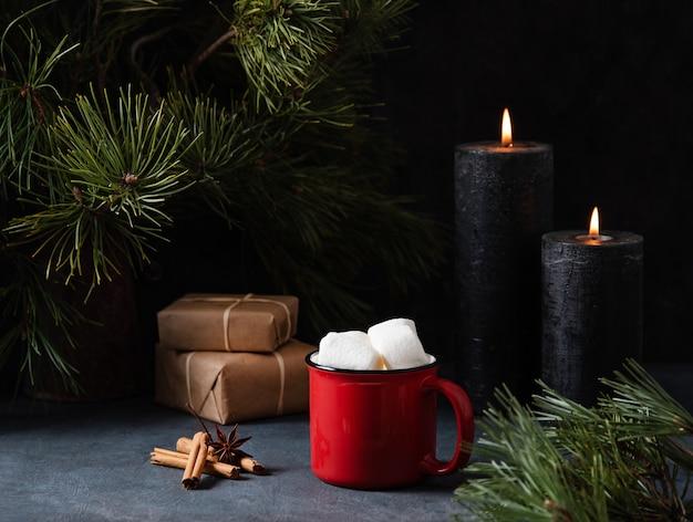 Caneca vermelha com cacau, marshmallow e canela em um fundo azul escuro com velas acesas, presentes e pinheiro. imagem escura e de humor