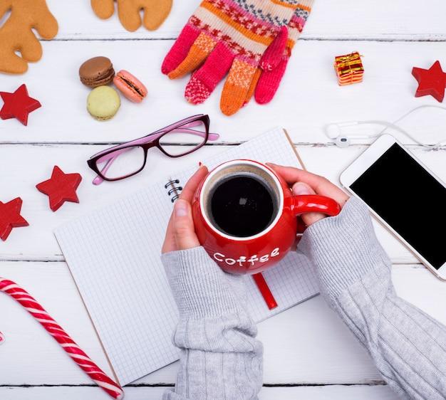 Caneca vermelha com café preto em mãos femininas sobre uma mesa