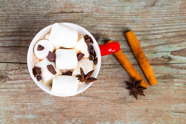 Caneca vermelha com chocolate quente com canela derretida de marshmallow e anis estrelado em fundo de madeira a vista de cima