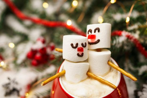 Caneca vermelha com chocolate quente e bonecos de neve apaixonados feitos de marshmallows.