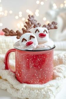 Caneca vermelha com chocolate quente e rena de marshmallow derretido