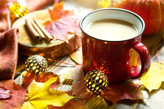 Caneca vermelha com chocolate quente na mesa com folhas de bordo caídas, lâmpadas redondas, guirlandas, paus de canela, cobertor quente. atmosfera de outono, café quente, mãos femininas em suéter branco, aconchego e conforto