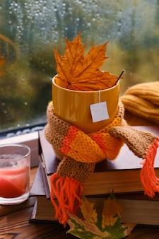 Caneca vermelha com um lenço e folhas secas no contexto da janela depois da chuva. aquecer bebidas de outono. mock up para design de chá