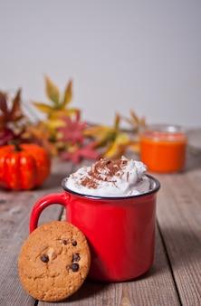 Caneca vermelha de cacau cremoso quente com espuma na mesa de madeira com biscoitos, folhas de outono, vela e abóbora