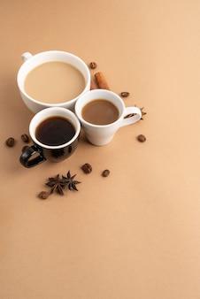 Canecas com café com canela e erva-doce ao lado