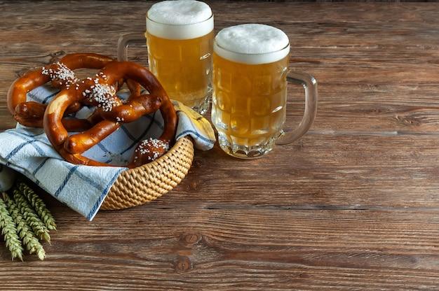 Canecas com cerveja e pretzels em uma cesta sobre uma mesa de madeira escura.