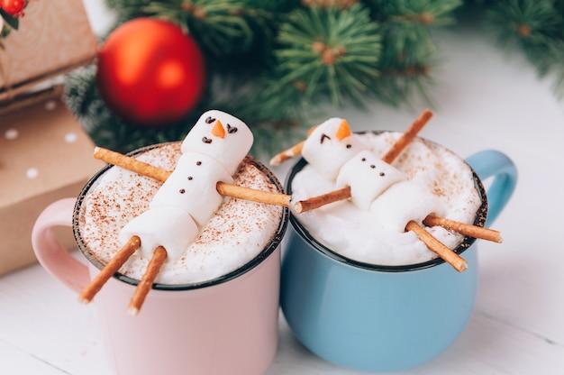Canecas com chocolate quente nas quais os homens do marshmallow relaxam. conceito de um casal