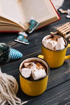 Canecas com marshmallows perto de brinquedos de Natal e livro