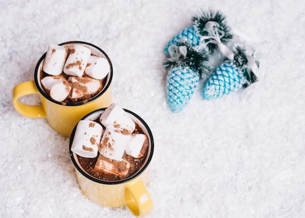 Canecas com marshmallows perto de brinquedos de natal entre a neve