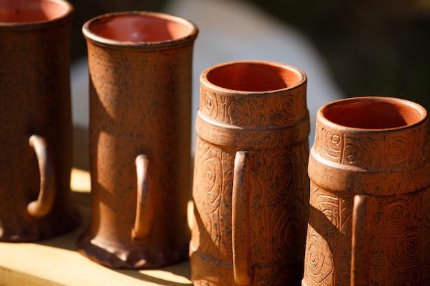 Canecas de argila marrom estão na prateleira. feito à mão