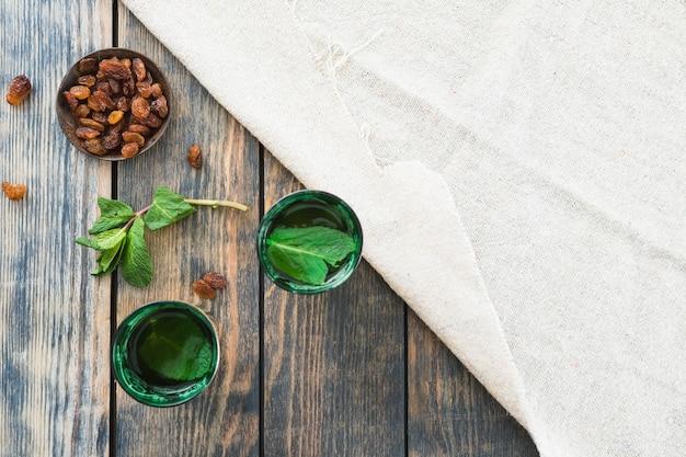 Canecas de bebida perto de frutas secas em pires e material