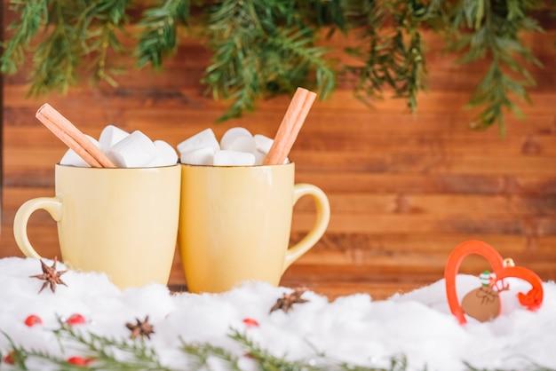 Canecas de cacau com marshmallows e paus de canela